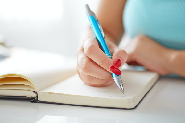 woman writes in notebook on a white table