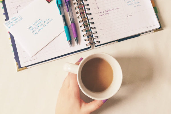 planner and pens on table and person holding coffee cup
