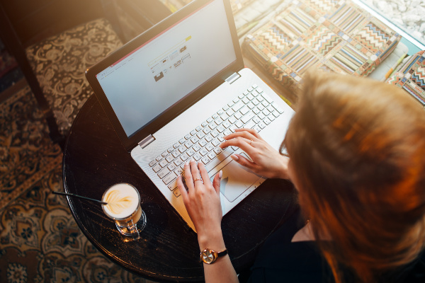 woman working on laptop with coffee