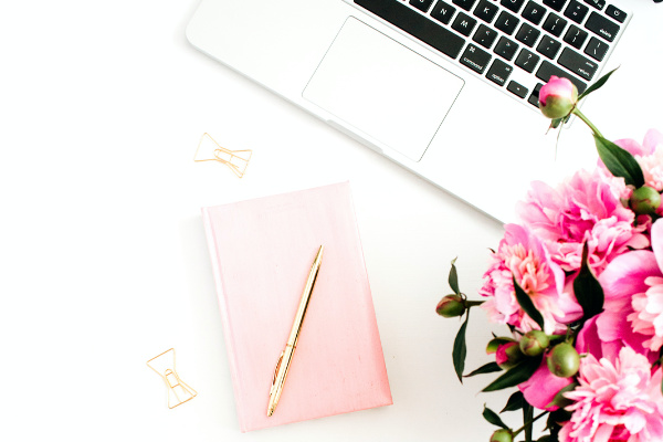laptop, pink peonies, pink notebook, and gold pen