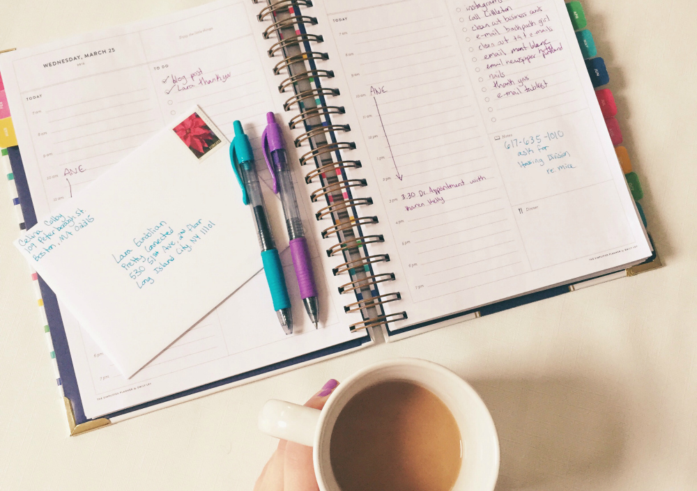 planner, pens and coffee on desk