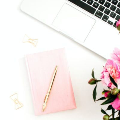 laptop, pink flowers and pink notebook on white desk