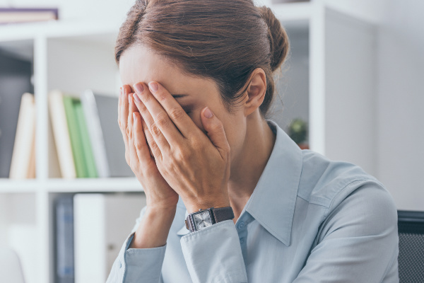 stressed women with head in hands in front of computer closeup