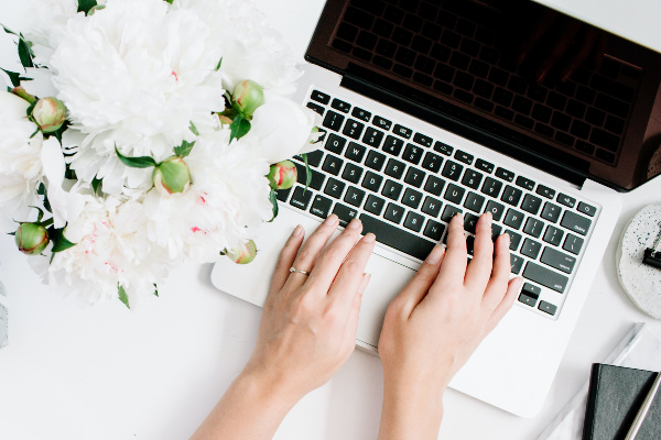 woman typing on laptop with white flowers