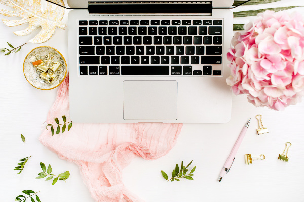 white desk with laptop, pink scarf, pink flowers, and gold accessories