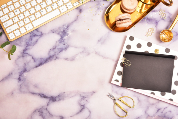 gold computer keyboard, polka dot notebook and gold accessories on purple marble background